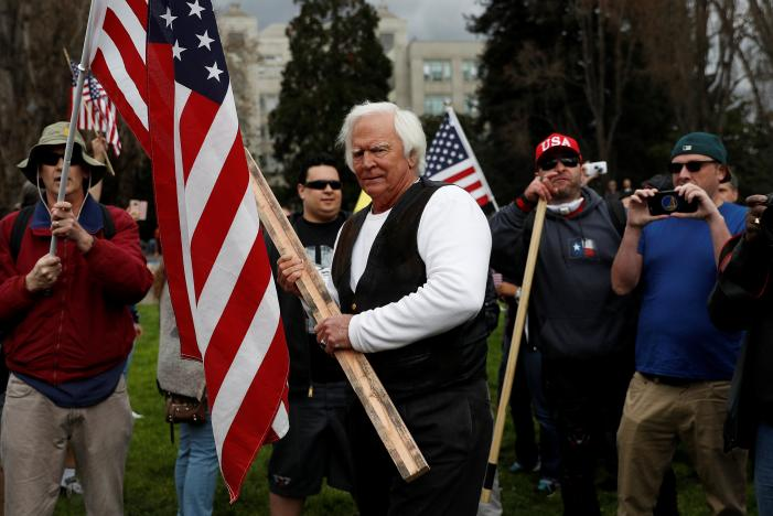 """A demonstrator in support of U.S. President Donald Trump holds a stick during a """"People 4 Trump"""" rally in Berkeley, California"""